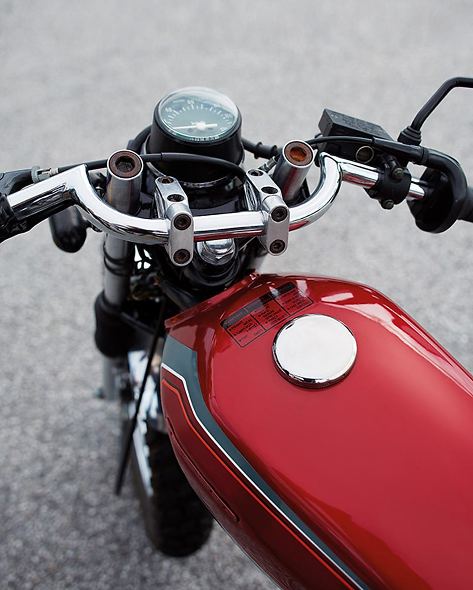 red motorcycle petrol tank with front wheel, handle bars, and speedometer